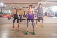 年轻小组三健身健身房重量酒吧 库存照片