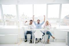 小组不同的设计师在他们的现代办公室 免版税库存照片