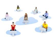 小组不同种族的人民坐与计算机的一朵云彩 库存图片
