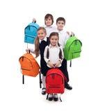 小组与五颜六色的书包的愉快的孩子 免版税库存照片