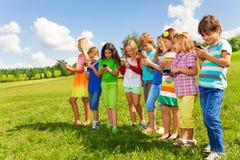 小组与电话的孩子 免版税库存照片
