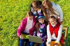 小组与膝上型计算机的青少年的孩子 免版税库存图片