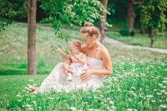 小组两个人、白白种人母亲和女婴孩子白色礼服坐的使用的在绿色夏天公园森林里外面 免版税库存照片
