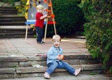 小组两个白白种人小孩孩子通过画画架哄骗男孩和女孩外面在夏天秋天公园 免版税库存照片