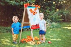 小组两个白白种人小孩孩子通过画画架哄骗男孩和女孩常设外部在夏天秋天公园 免版税库存图片