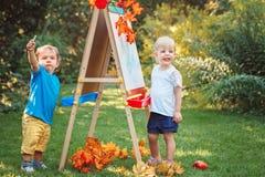 小组两个白白种人小孩孩子通过画画架哄骗男孩和女孩常设外部在夏天秋天公园 免版税库存照片