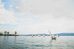 小组乐观主义者类小船的年轻运动员  免版税库存照片