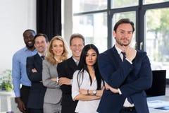 小组买卖人在有男性领导人的创造性的办公室在前景商人和女实业家成功的队 库存照片