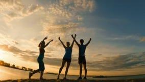 小组年轻人和妇女-运动员-两个女孩和人是有在山的胜利,靠近河在黄昏 免版税图库摄影