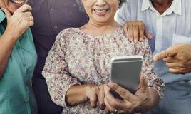 小组使用数字式生活方式概念的资深退休 免版税库存照片