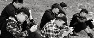 小组使用他们的手机的脊椎人户外 免版税库存图片