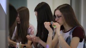 小组俏丽的女孩坐在桌上并且保重关于他们的手的 影视素材