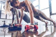 小组做与哑铃的运动服的运动青年人俯卧撑在健身房 图库摄影