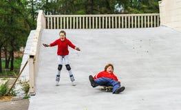 小组儿童四轮溜冰在公园 免版税库存照片