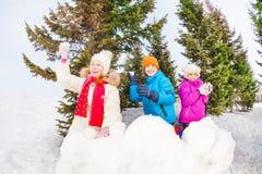 小组儿童游戏雪球比赛在森林里 免版税库存图片