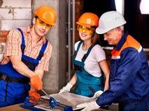 小组切开陶瓷砖的人建造者。 免版税库存照片