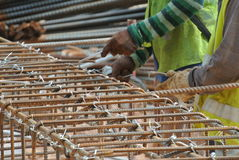 小组制造桩帽钢增强酒吧的建筑工人 免版税库存图片
