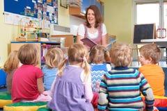 小组前听老师读书故事的小学生 免版税图库摄影
