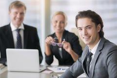 小组商人和一个微笑的年轻人 免版税图库摄影