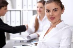 小组商人在关于办公室背景的会议上  在一个美丽的浅黑肤色的男人的焦点 免版税库存图片