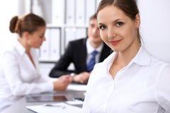 小组商人在关于办公室背景的会议上  在一个美丽的浅黑肤色的男人的焦点 免版税库存照片