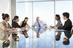 小组商人开委员会会议在玻璃表附近 库存图片