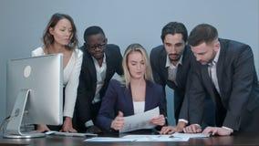小组商人繁忙的谈论的金融事件在会议期间,站立在女性上司书桌附近 图库摄影