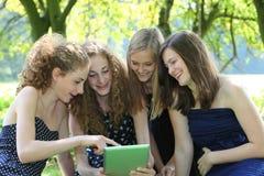 小组四可爱的年轻少年与片剂个人计算机一起使用 免版税库存照片
