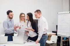 小组四名不同的男人和妇女便衣的谈话在办公室 图库摄影