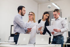 小组四名不同的男人和妇女便衣的谈话在办公室 免版税库存图片