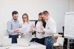 小组四名不同的男人和妇女便衣的谈话在办公室 库存图片