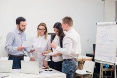 小组四名不同的男人和妇女便衣的谈话在办公室 免版税库存照片