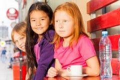 小组国际孩子坐在咖啡馆外面 免版税图库摄影