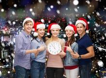 小组圣诞老人帮手帽子的少年有时钟的 库存图片