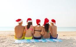 小组圣诞老人帮手帽子的朋友在海滩 免版税库存图片