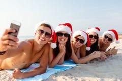 小组圣诞老人帽子的朋友有智能手机的 免版税库存照片