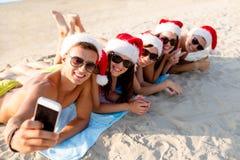 小组圣诞老人帽子的朋友有智能手机的 图库摄影