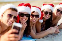 小组圣诞老人帽子的朋友有智能手机的 库存照片