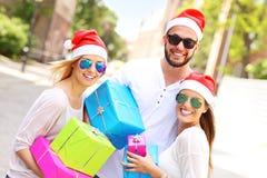 小组圣诞老人的帽子的朋友有礼物的 库存图片