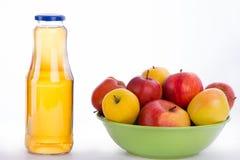 小组在一个绿色板材和瓶的苹果在白色ba的汁液 库存图片