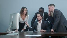 小组在会议桌附近的多种族商人看便携式计算机和谈话与互相 股票录像