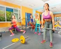 小组在健身俱乐部的女孩deadlift 库存照片