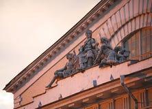 小组在古色古香的样式的寓言的雕塑 在老历史建筑的门面的装饰雕刻的元素 免版税库存照片