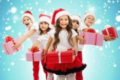 小组在圣诞节帽子的愉快的孩子有礼物的 免版税库存图片
