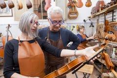 小组在姿势的成熟小提琴制造商 免版税图库摄影