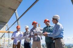 小组在安全帽的建造者谈论项目图纸与的建造场所的建筑师 库存照片