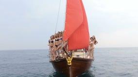 小组在放松在有红色风帆的豪华游艇的比基尼泳装的苗条模型在公海 影视素材