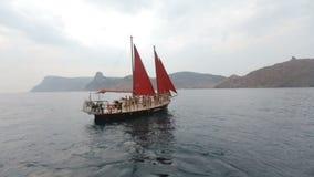 小组在放松在有红色风帆的豪华游艇的比基尼泳装的苗条模型在公海 股票视频