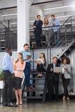 小组在楼梯的商人,成功的队谈论新的项目战略在现代打开 库存照片