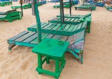 小组在海滩的空的绿色sunbeds。 免版税库存图片